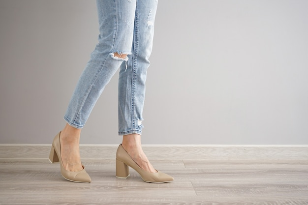 Legs of a young woman in jeans and shoes on gray background, space for text.