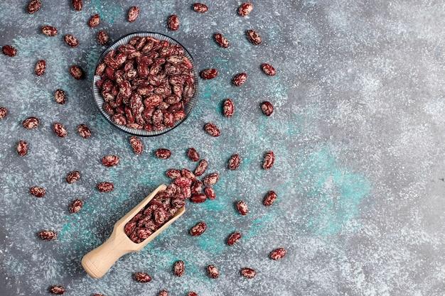 가벼운 돌 표면에 다른 그릇에 콩과 콩 구색. 평면도. 건강한 비건 단백질 식품.