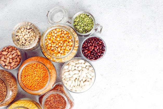 Ассорти бобов и фасоли в разных мисках на светлом камне. вид сверху. здоровая веганская белковая пища.