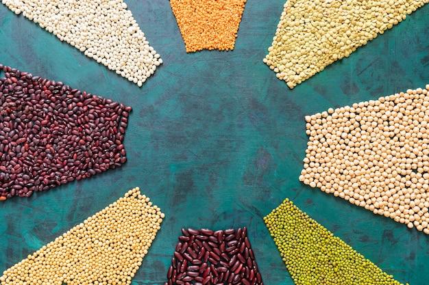 マメ科植物と穀物は、エメラルドグリーンの背景に太陽光線のように配置されています。