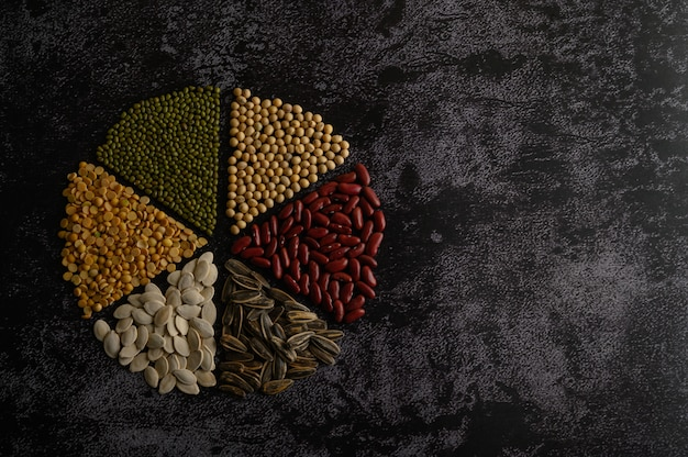 Legumes arranged in a circle on the black cement floor.