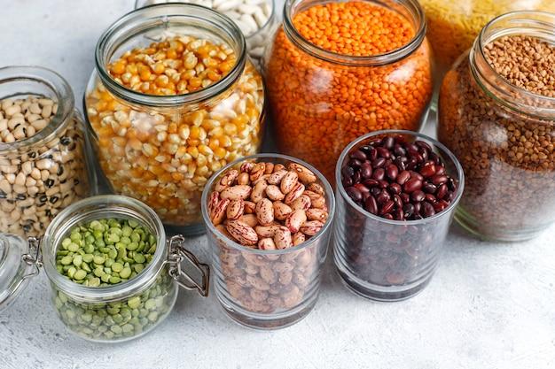 Assortimento di legumi e fagioli in diverse ciotole su fondo in pietra chiara. vista dall'alto. alimento proteico vegano sano.