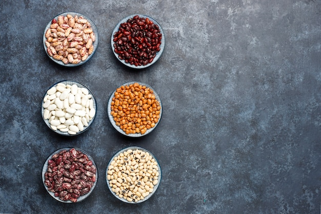 Legumes and beans assortment in different bowls on light stone surface . top view. healthy vegan protein food.