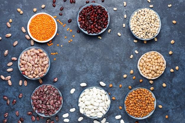 Assortimento di legumi e fagioli in diverse ciotole sulla superficie della pietra chiara. vista dall'alto. alimento proteico vegano sano.