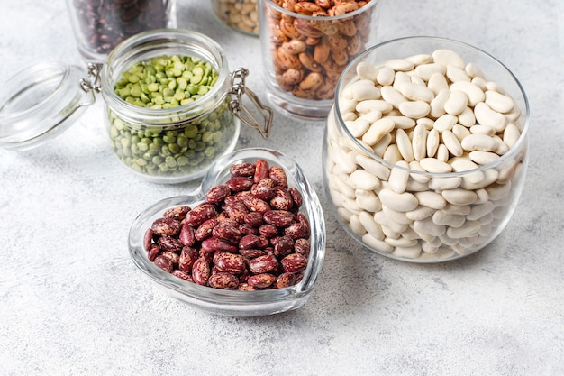 Legumes and beans assortment in different bowls on light stone