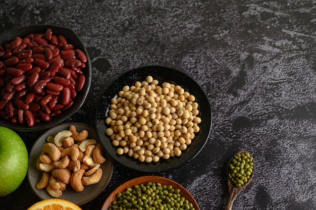 Legumes and fruit on a black cement floor surface.