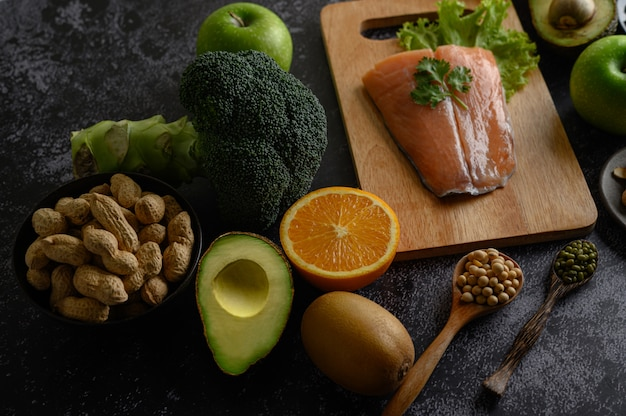Legumes, fruit, and salmon fish pieces on a wooden chopping board.