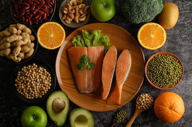 Legumes, fruit and salmon pieces on a wooden plate.