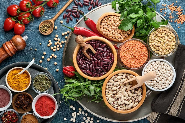 Legumes, lentils, chickpea, beans assortment, tasty appetizing ingredients spices grocery for cooking healthy kitchen on black table