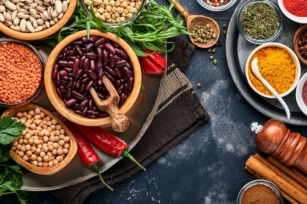 マメ科植物、レンズ豆、ひよこ豆、豆の品揃え、おいしい食欲をそそる食材は、黒いテーブルで健康的なキッチンを調理するための食料品をスパイスします。減量ダイエットとコレステロールの概念との戦い。上面図。