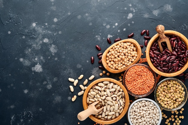 Legumes, red lentils, chickpea, red and white beans assortment in different bowls