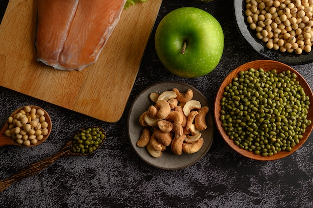 Legumes, salmon pieces and apple on a black cement floor surface.