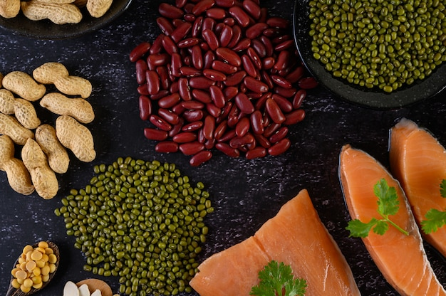 Legumes and salmon placed on a black cement floor.