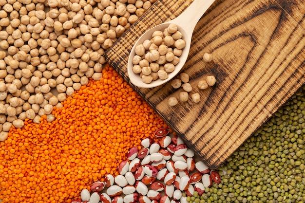 マメ科植物、さまざまな豆、レンズ豆、エンドウ豆の背景、上面図のセット。健康食品とプロテインフードのコンセプト。