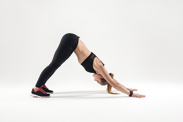 Leisure active woman doing asana and have a harmony. studio shot, gray background