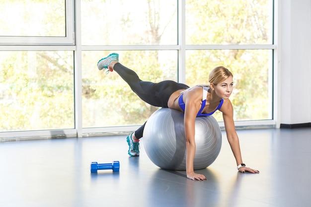 여가 활동적인 여성은 체조를 하고 공 위에 누워 있습니다. 스튜디오 촬영