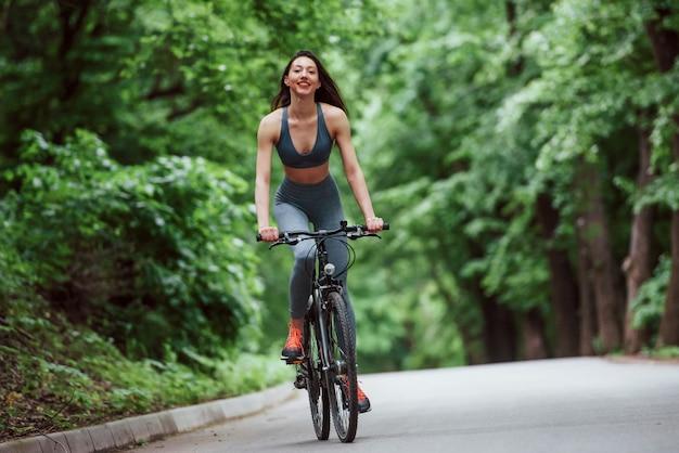 余暇活動。昼間の森の中のアスファルトの道路上の自転車の女性サイクリスト