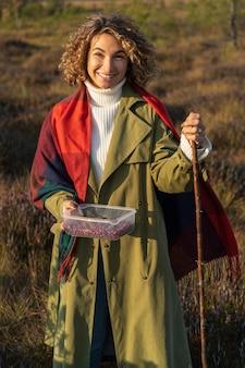 자연에서의 여가 활동 젊은 행복한 여성이 늪에서 가을 숲을 걷는 크랜베리 따기