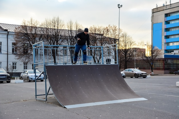 夕焼けの街の中心部でのレジャー活動男ローラースケート。冬。ストリートローラースケート。