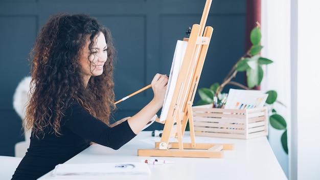 余暇と創造。ホームスタジオで絵を楽しんでいる巻き毛の才能のある女性