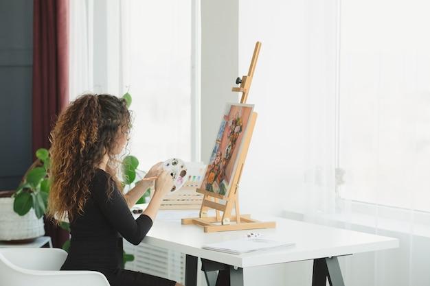 Досуг и творчество. талантливая дама с вьющимися волосами наслаждается рисованием в домашней студии