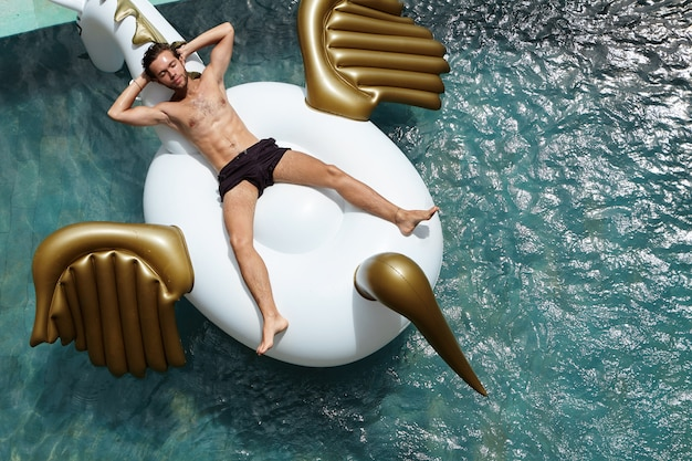 レジャーとレクリエーションのコンセプトです。待望の休暇を楽しんでいるインフレータブルドラゴンマットレスの上に横たわるフィット体で若い男のトップビュー