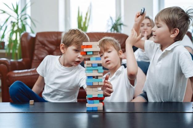 백인 가족의 여가와 편안한 라이프 스타일. 어린 형제들은 집에서 즐겁게 보드게임을 하며 경쟁합니다.