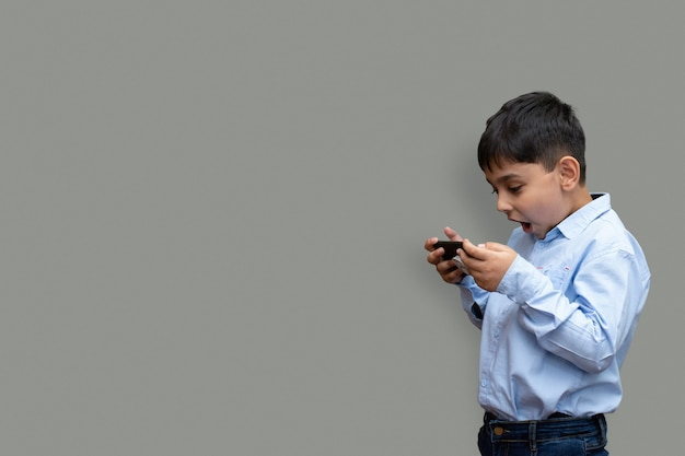 Leisure, children, technology and people concept - smiling boy with smartphone  or playing game at home copy space