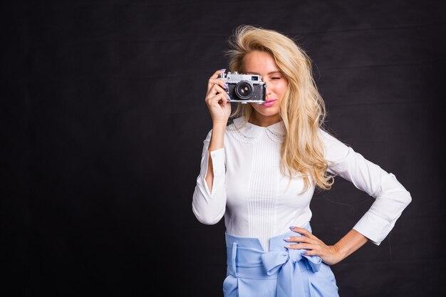 Досуг, мода и люди концепции молодая блондинка женщина, стоящая на черном фоне