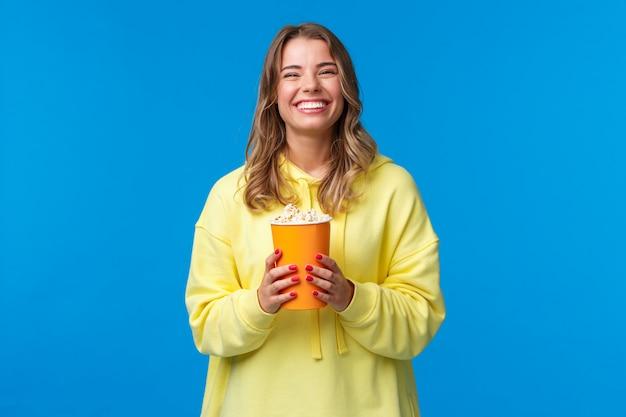 Досуг, веселье и молодежная концепция. дружелюбная счастливая белокурая европейка наслаждается выходными, ест попкорн и смотрит комедию, посещает кино, чтобы посмотреть новый фильм, стоит
