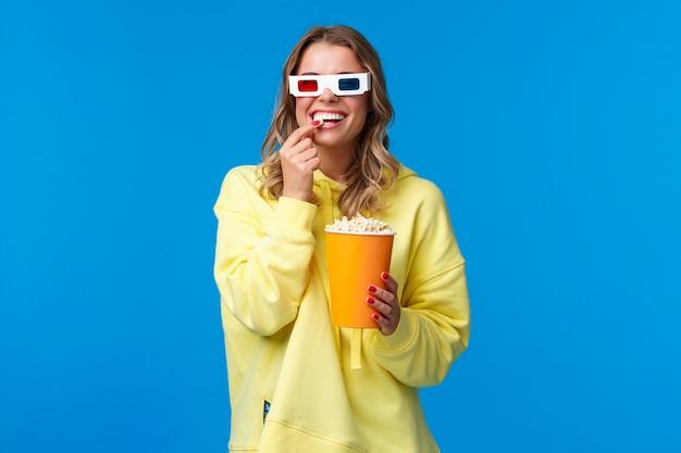 Концепция досуга, веселья и молодости счастливая развлеченная улыбающаяся белокурая девушка в 3d очках, ест попкорн и смеется, как смотрит смешную комедию, идет в кино, смотрит фильм с друзьями