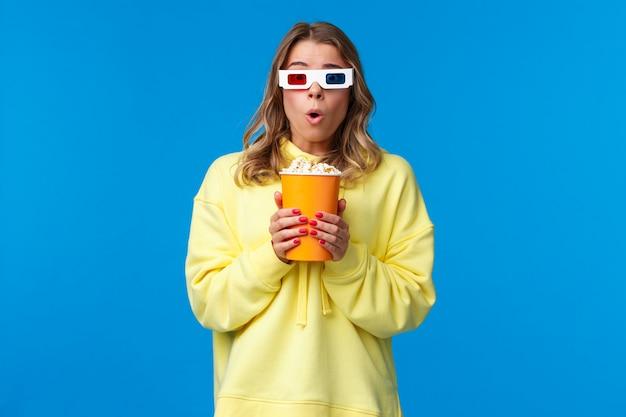 Досуг, веселье и молодежная концепция. безмолвная изумленная молодая взволнованная девушка со светлыми волосами в 3d-очках, держащая попкорн, говорит, что удивленно задыхаясь, смотрит триллер в кино