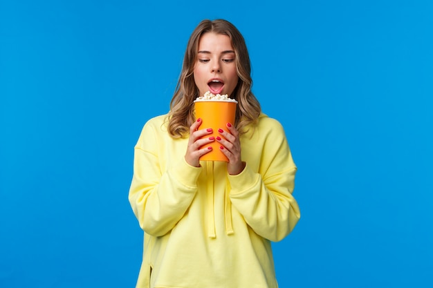 Leisure, fun and youth concept. girl likes eating popcorn in cinema, have bite and staring at can with desire, watching movie, standing  in yellow hoodie