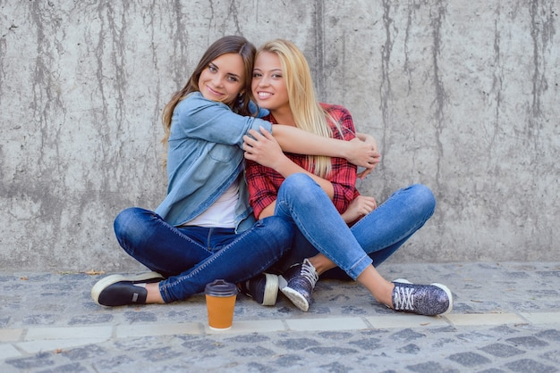 Leisure funtime shoes sneakers takeaway to go mug tea shop feelings face emotion expressing concept. portrait of nice glad beautiful pretty cute cool adorable hugging girls isolated on gray background