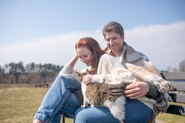 余暇、調和。格子縞の屋外行楽客の若い大人の男性と素晴らしい気分の猫と女性