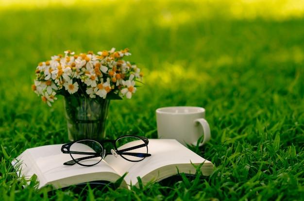 Отдых утром в саду с кофе, книгой и цветами на лужайке