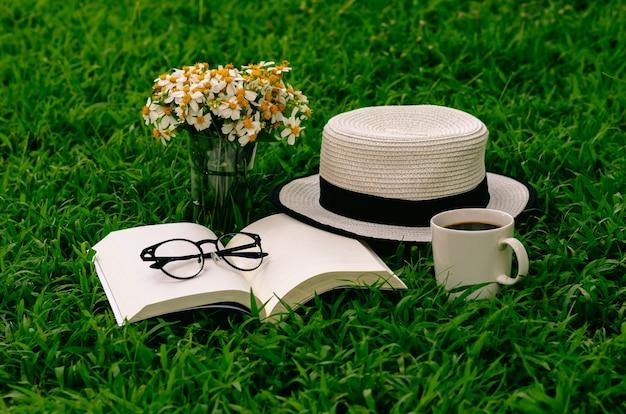 Отдых утром в саду с кофе, книгой, шляпой и цветами на лужайке.