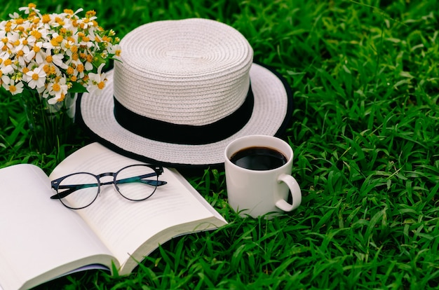 Отдых утром в саду с кофе, книгой, шляпой и цветами на лужайке