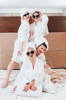 余暇の喜び。ベッドでポーズをとる陽気な女性。サングラス、バスローブ、タオルターバン。週末の時間。