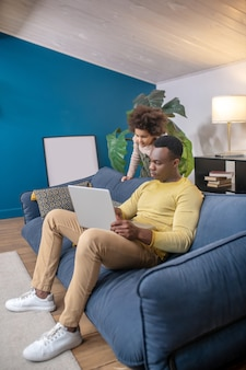 Leisure, laptop. darkskinned young adult dad in casual clothes with laptop sitting on sofa at home and interested little cute daughter behind