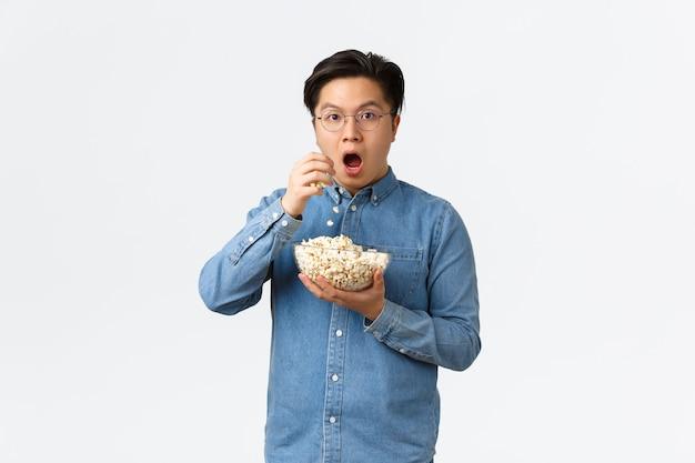 余暇のライフスタイルと人々のコンセプトは、素晴らしい映画やテレビのセリを見ている興奮して驚いたアジア人の男...