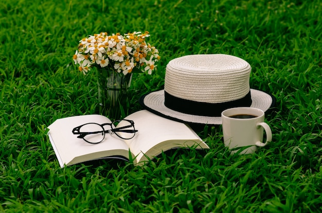 Leisure in morning at garden with coffee, book , hat and flowers on the lawn.