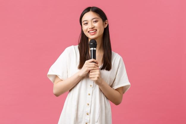 余暇、人々の感情とライフスタイルの概念。カラオケで陽気な笑顔のアジアの女の子、週末を楽しんで、マイクで歌を歌い、スタンドアップ、立っているピンクの背景を実行します。