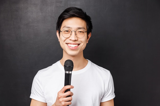 Leisure, people and music concept. handsome and cute smiling asian man in white t-shirt, glasses, holding microphone, singing at karaoke party with friends, picking song on screen,