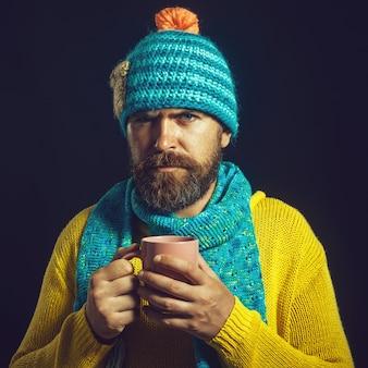 レジャーの人々は、マグカップでコーヒーティーの水を飲むハンサムな魅力的なひげを生やした男がホットドリンクを味わう
