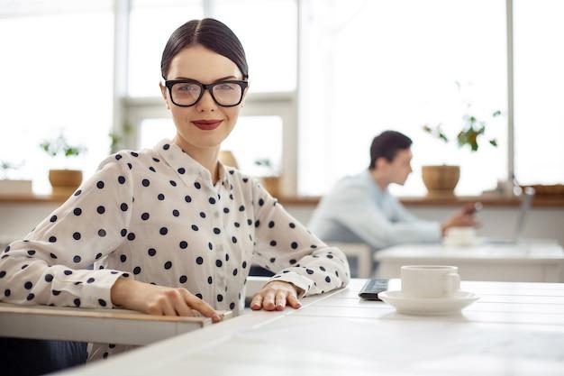 Досуг. довольно веселая темноволосая молодая женщина улыбается и пьет кофе, сидя за столом