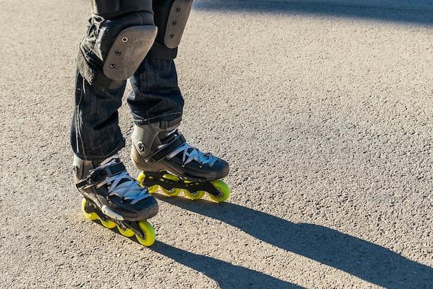 レジャー、スポーツ、人々の概念-道路でローラースケートスケートの足のクローズアップ