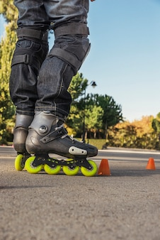 Leisure, sport and people concept - close up of legs in rollerskate skating on road from back