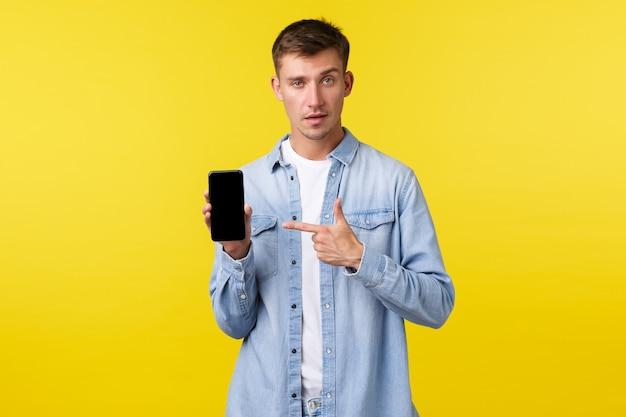Рекламная концепция досуга, технологий и приложений. крутой красивый белокурый мужчина в повседневной одежде, указывая пальцем на экран смартфона, показывает дисплей мобильного телефона, чтобы рекомендовать приложение.