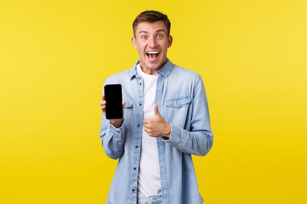 Рекламная концепция досуга, технологий и приложений. взволнованный, счастливый и довольный блондин показывает палец вверх и рекомендует супер классное новое приложение, показывая онлайн-скидки на экране мобильного телефона.